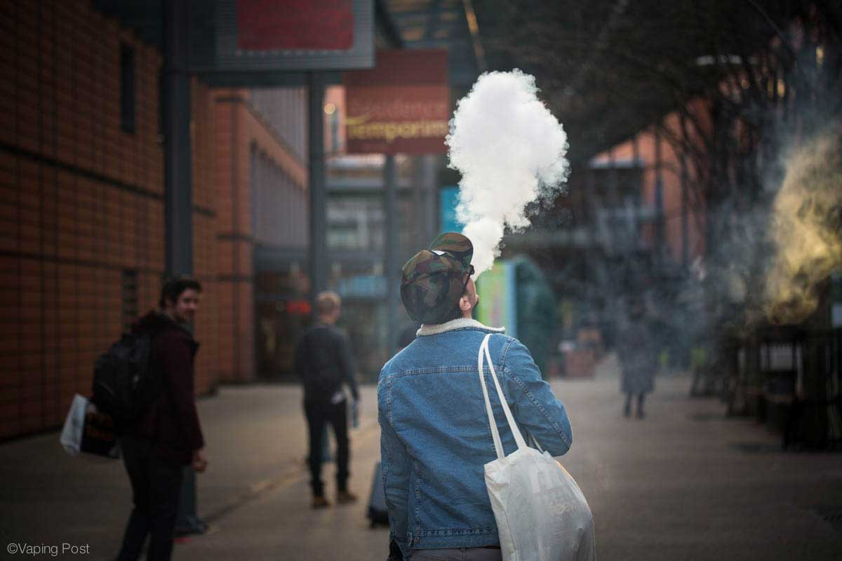 A vaper on the street blowing a giant cloud