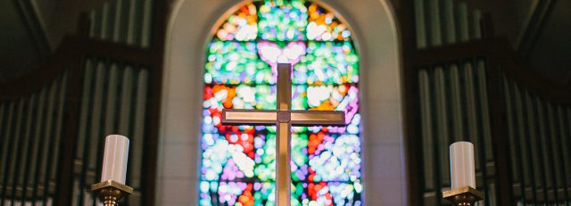 A cross in a church with a stained glass bokeh in the background
