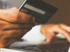 man holding his credit card to shop online