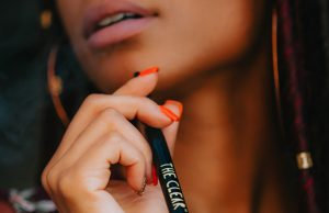 Close up of woman with manicured hand holding the clear vape pen