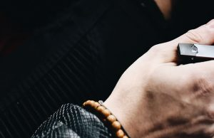 man holding a Juul e-cig