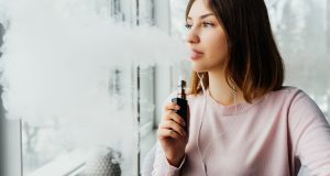 woman vaping while listening music