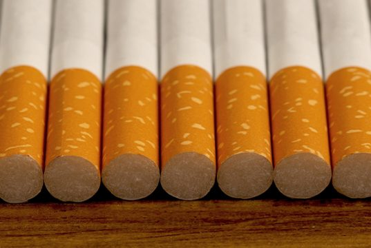 Many cigarettes stacked on wooden floor