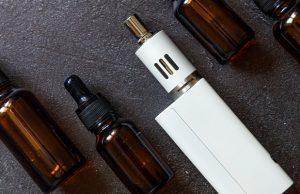 Vaping device e-cigarette electronic cigarette and liquid bottles on dark black stone shale background